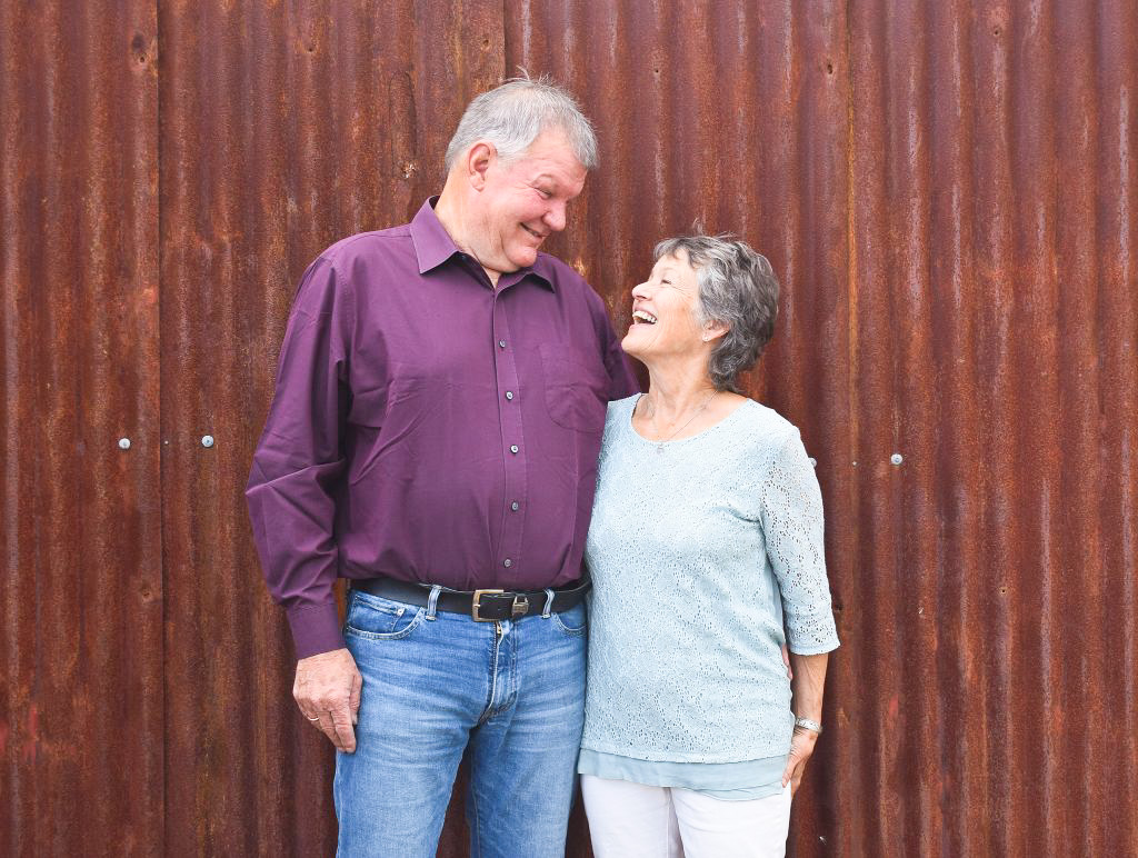 An image of Sue and Jeff Allen standing in front of some rusted sheeting